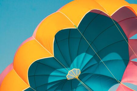 Close Multi-colored Parachute For Parasailing On Background Of Blue Sky.