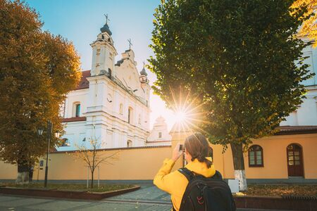 Pinsk, Brest Region, Belarus. Young Woman Tourist Lady Photograph Taking Pictures Near Cathedral Of Name Of The Blessed Virgin Mary. Famous Historic Landmarks. Sun Sunshine In Autumn Sunny Day. Foto de archivo