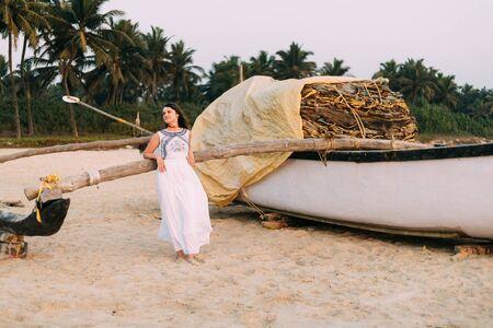 Goa, India. Young Caucasian Woman In White Dress Standing Near Fishing Boat And Posing For Camera. Foto de archivo