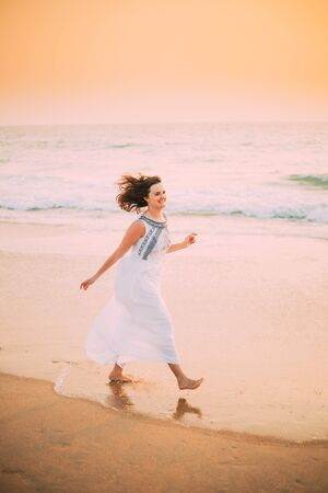 Goa, India. Young Caucasian Woman With Fluttering Hair In Wind In White Dress Walking Along Seashore, Enjoying Life And Smiling In Summer Sunlight