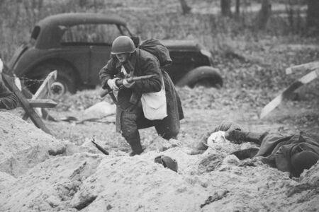 Re-enactor Dressed As Red Army Russian Soldier Of World War II Running On Battlefield 免版税图像
