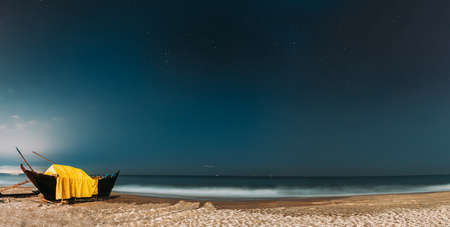 Goa, India. Real Night Sky Stars. Natural Starry Sky Blue Color Above Sea Seascape Ocean Beach. Background. Parked Old Wooden Boat At Coast. Panorama, Panoramic View.