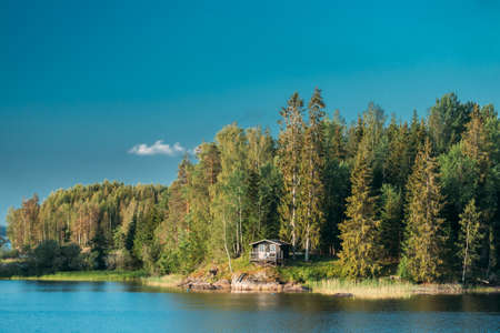 Sweden. Beautiful Swedish Wooden Log Cabin House On Rocky Island Coast In Summer Sunny Evening. Lake Or River Landscape. 스톡 콘텐츠