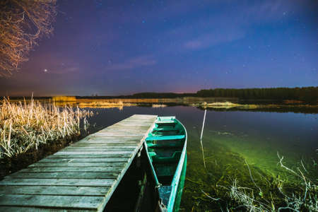 Real Night Sky Stars Above Old Pier With Moored Wooden Fishing Boat. Natural Starry Sky And Countryside Landscape With Lake River In Early Spring Night. Russian Nature.