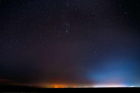 Night Starry Sky With Glowing Stars Above Countryside Landscape. Rural Field Meadow In Early Spring. Bright Glowing Stars