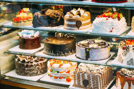Various Different Types Of Sweet Cakes In Pastry Shop Glass Display. Good Assortment Of Confectionery 版權商用圖片