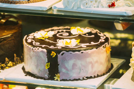 Fresh Sweet Cake With Different Chocolates In Pastry Shop Glass Display