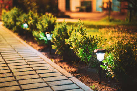 Night View Of Flowerbed Illuminated By Energy-Saving Solar Powered Lanterns Along The Path Causeway On Courtyard Going To House.