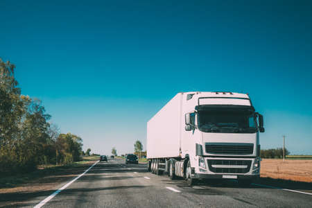 Truck On Country Road. Tractor Unit, Prime Mover, Traction Unit In Motion On Countryside Road In Europe. Business Transportation And Trucking Industry Concept