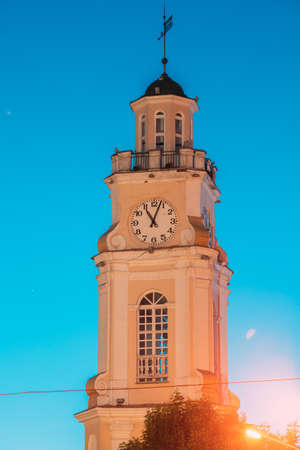 Vitebsk, Belarus. Close Up Of Old Town Hall. City Hall, Clock Tower Is Famous Landmark In Evening Time On Blue Hour Sky Background