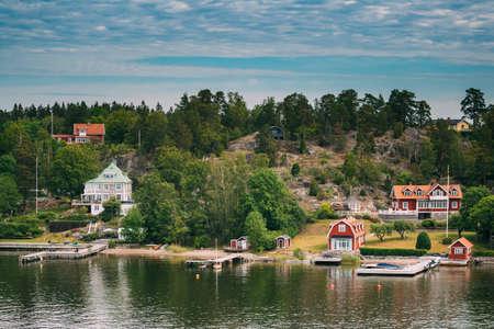 Sweden. Beautiful Red Swedish Wooden Log Cabin House On Rocky Island Coast In Summer Sunny Evening. Lake Or River Landscape Reklamní fotografie