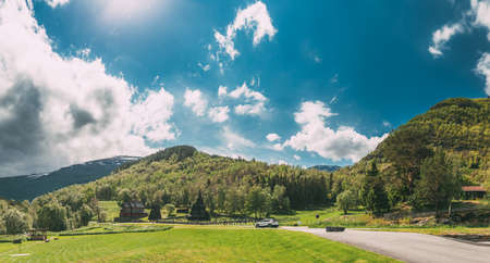 Borgund, Norway. Famous Landmark Stavkirke An Old Wooden Triple Nave Stave Church In Summer Day. Bright Sun Shines Over Ancient Old Worship. Norwegian Countryside Landscape. Panorama Panoramic View.