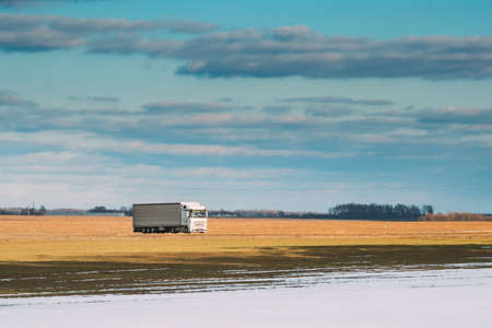 Truck Or Tractor Unit, Prime Mover, Traction Unit In Motion On Road Through Field Spring Field Partly Covered Melting Snow. Business Transportation And Trucking Industry