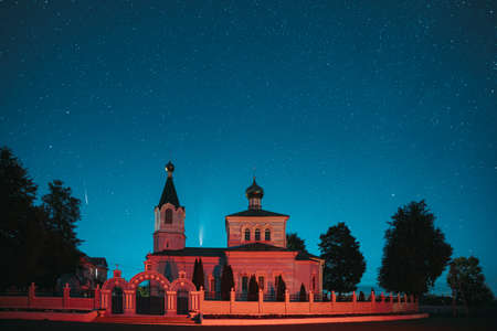 Korma Village, Dobrush District, Belarus. Comet Neowise C2020F3 And Meteor In Night Starry Sky Above St. John The Korma Convent Church In Korma Village. Famous Orthodox Church And Historic Heritage