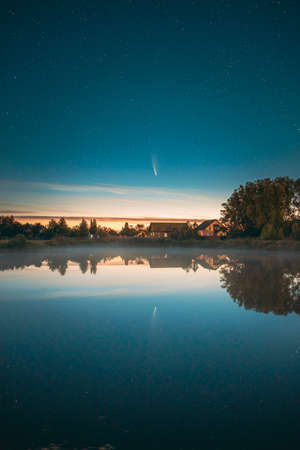 Dobrush, Belarus. Comet Neowise C2020f3 In Night Starry Sky Reflected In Small Lake Waters. 版權商用圖片