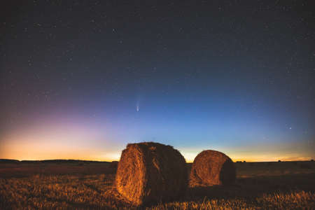 Comet Neowise C2020 F3 In Night Starry Sky Above Haystacks In Summer Agricultural Field. Night Stars Above Rural Landscape With Hay Bales After Harvest. Agricultural Concept