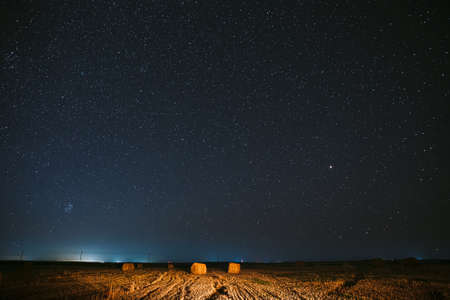 Night Starry Sky Above Haystacks In Summer Agricultural Field. Night Stars Above Rural Landscape With Hay Bales After Harvest. Agricultural Concept 版權商用圖片