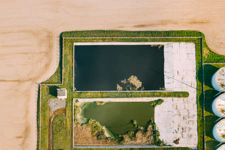 Aerial View Of Retention Basins, Wet Pond, Wet Detention Basin Or Stormwater Management Pond Near Biogas Bio-gas Plant From Pig Farm. Artificial Pond With Vegetation Around Perimeter.