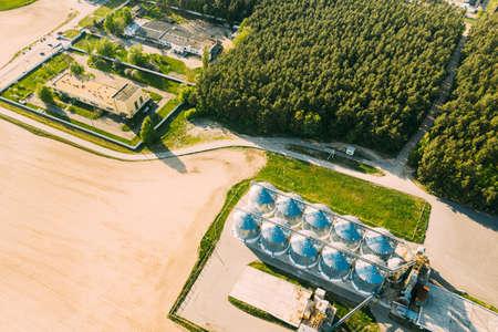 Aerial View Modern Granary, Grain-drying Complex, Commercial Grain Or Seed Silos In Sunny Spring Rural Landscape. Corn Dryer Silos, Inland Grain Terminal, Grain Elevators Standing In A Field 版權商用圖片