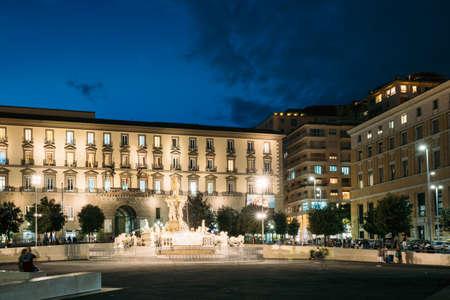 Naples, Italy. Fountain Of Neptune On Piazza Municipio In Evening Or Night Illuminations