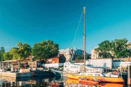 Riga, Latvia. Old Yacht Moored At The City Pier Harbour Bay And Quay In Summer Sunny Evening. Reflections From Boats In Water Of Western Dvina River