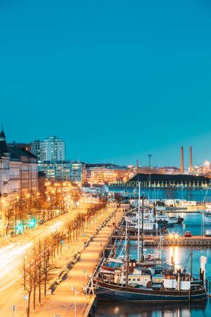 Helsinki, Finland. View Of Pohjoisranta Street And Ships, Boats And Yachts Moored Near Pier In Evening Night Illuminations