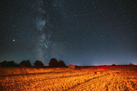 Milky Way Galaxy In Night Starry Sky Above Haystack In Summer Agricultural Field. Night Stars Above Rural Landscape With Hay Bale After Harvest. Agricultural Concept Banque d'images