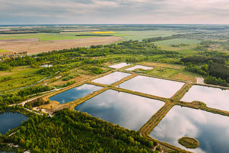 Aerial View Retention Basins, Wet Pond, Wet Detention Basin Or Stormwater Management Pond, Is An Artificial Pond With Vegetation Around The Perimeter, And Includes A Permanent Pool Of Water In Its Design. Stock Photo
