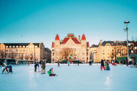 Helsinki, Finland. Children Skating On Rink On Railway Square On Background Of Finnish National Theatre In Winter Sunny Day
