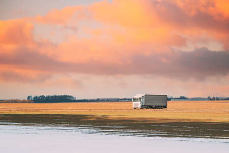 Truck Or Tractor Unit, Prime Mover, Traction Unit In Motion On Road Through Field Spring Field Partly Covered Melting Snow. Business Transportation And Trucking Industry. Altered Sky