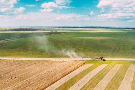 Aerial View. Tractor Plowing Field In Spring Season. Beginning Of Agricultural Spring Season. Cultivator Pulled By A Tractor In Countryside Rural Field Landscape