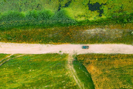Aerial View Of Car SUV Parked On Countryside Road Between Rural Field And Marsh Bog Swamp Landscape. Summer Day