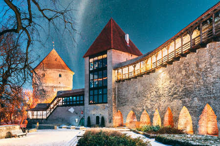 Tallinn, Estonia. Night Starry Sky Above Traditional Old Architecture Skyline In Old Town. Former Prison Tower Neitsitorn In Winter Evening Night. Famous Landmark. Altered Sky With Stars