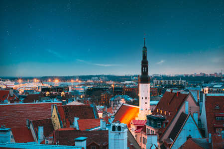 Tallinn, Estonia. Night Starry Sky Above Traditional Old Architecture Skyline In Old Town. Church Of Holy Ghost Or Holy Spirit In Winter Evening. Landmark   Site. Altered Sky Stars