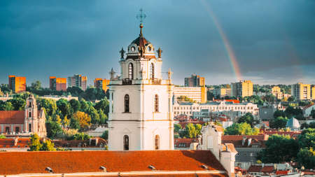 Vilnius, Lithuania. Sunset Cityscape Of Vilnius, Lithuania In Summer. Beautiful View Of Old Town In Evening. Sts Johns Church Sv. Jonu baznycia . Altered Sky With Rainbow