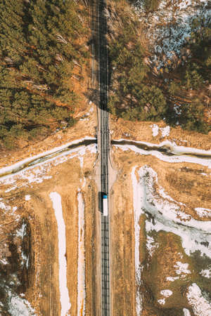 Aerial View Of Highway Road Through Spring Forest Landscape. Top View Of White Truck Tractor Unit Prime Mover Traction Unit In Motion On Freeway. Business Transportation, Trucking Industry. Flat View