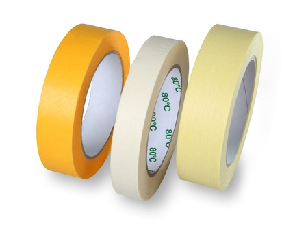 masking: Three rolls of narrow masking tape, yellow, white and brown, standing at his side, isolated on a white background. Stock Photo