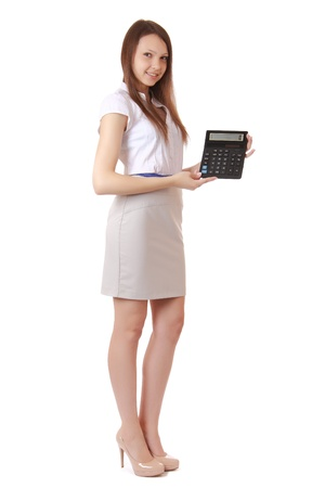 Girl, 16 years old, shows digits on calculator display  Portrait of a girl, full-length auburn hair, a gray skirt, shirt with short sleeves  The girl smiles  The isolated image on a white background, vertical orientation  photo