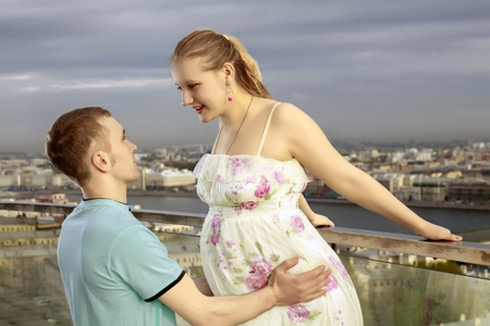 Happy couple on the roof of a high building, with views of the big city. Stock Photo