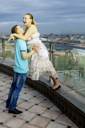 Happy couple on the roof of a high building, with views of the big city