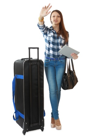 16 years: Teen girl 16 years old, with a big, black travel bag on wheels. Young traveler with a huge, black travel bag on wheels, waving his hand, drawing the attention of greeters. One person, female, vertical image, isolated on white background.