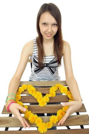 beguin: teen girl holds a heart of yellow dandelion flowers