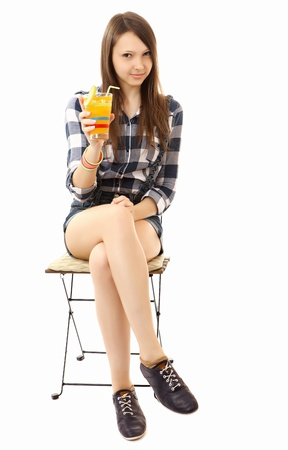 Teen Girl relaxing sitting on the folding chair with a cocktail in hand. One person, brown hair, caucasian appearance, teenage girl, female, 16 years old, vertical image, isolated on white background.  Stock Photo