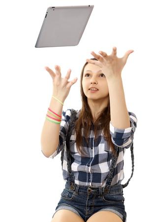 chemise carreaux: Fille attrape voler dans l'air Tablet PC. Caucase adolescente, v�tue d'une chemise � carreaux et short en jean, jette dans la tablette PC air. Une personne, adolescent, femme, caucasien, vertical, isol�. Banque d'images