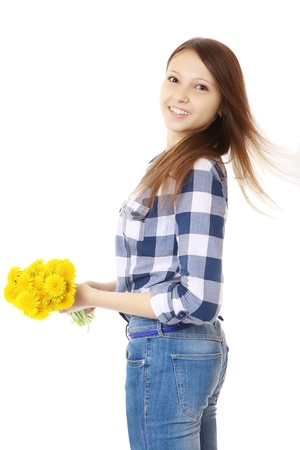 16 year old girls: Girl dressed in jeans and a plaid shirt, holds a yellow wildflowers. Girl with bouquet of dandelions. One person, Caucasian appearance, brown hair, teenager, female, vertical image, isolated on white background. Stock Photo