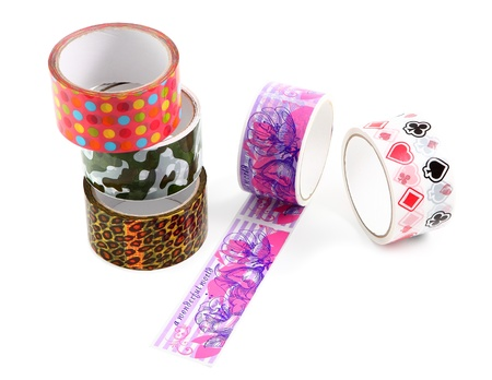 Set of several rolls of colored packing tape with colorful decorative print. Polka dot print, camouflage print, animal print, leopard print.