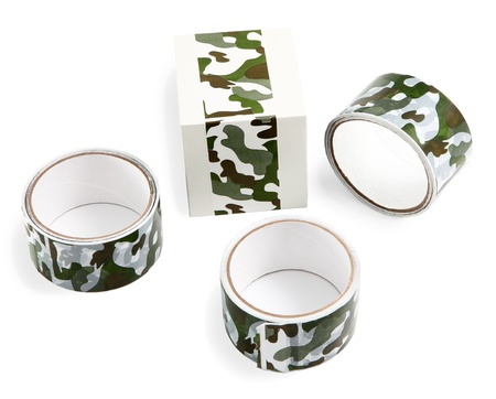 Three rolls of duct tape with print green camouflage and a box wrapped with ribbon for packing purchases and gifts. Flexible packaging materials and products.
