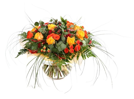 incarnadine: Flower arrangement of orange roses, hypericum and fern. Floral composition in a transparent glass vase. Isolated on white.
