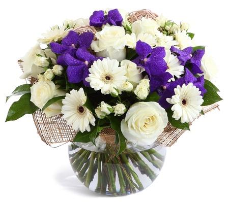 floristic: Flower arrangement in glass, transparent vase: White roses, purple orchids, white gerbera daisies, green peas. Isolated on white background. Floristic composition, design a bouquet, floral arrangement. Violet orchids. Stock Photo