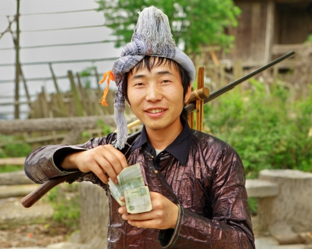 GUIZHOU PROVINCE; CHINA - APRIL 10: Man Miao ethnic group, with a musket on his shoulder, counts Yuan earned at village festival., April 10, 2010. Basha Miao Ethnic minority Village, Congjiang County
